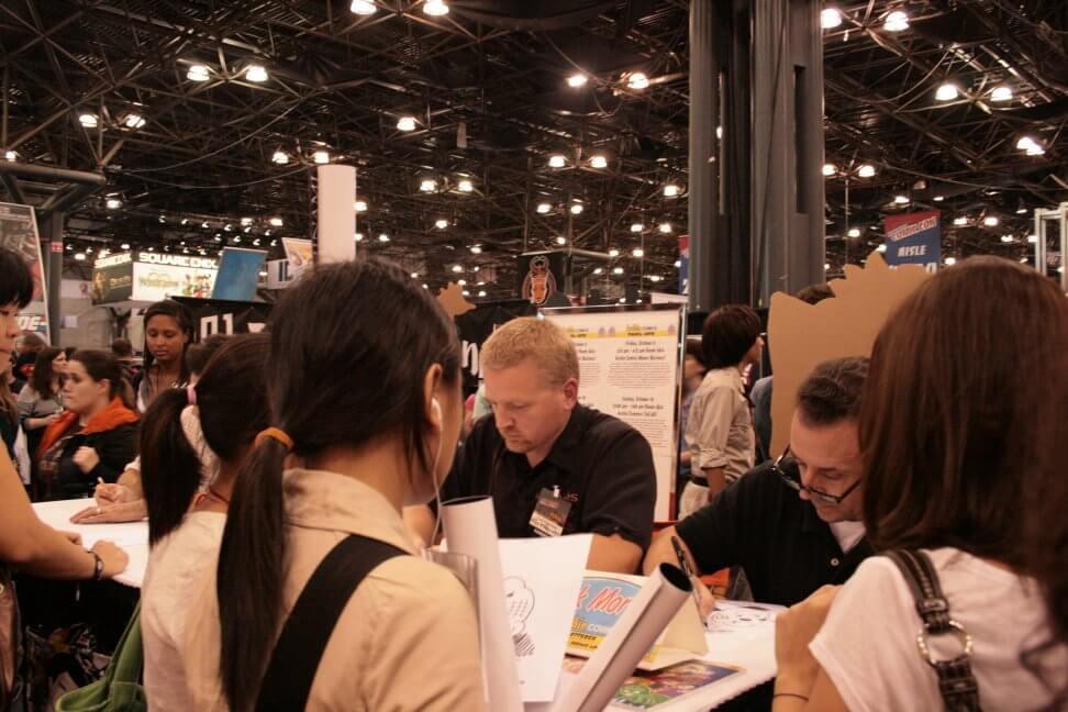 Rich Koslowski signing comics at comic convention table